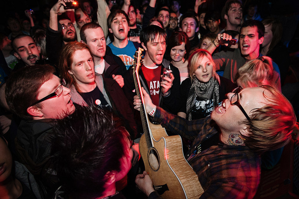 Kris Roe of The Ataris playing acoustic guitar in a crowd photographed by Marcus Maschwitz