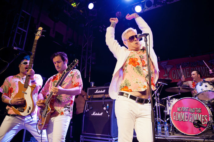 Me First and the Gimme Gimmes playing live on stage in white suits photographed by Marcus Maschwitz