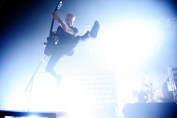 Zach Blair of Rise Against jumping at Brixton Academy photographed by Marcus Maschwitz
