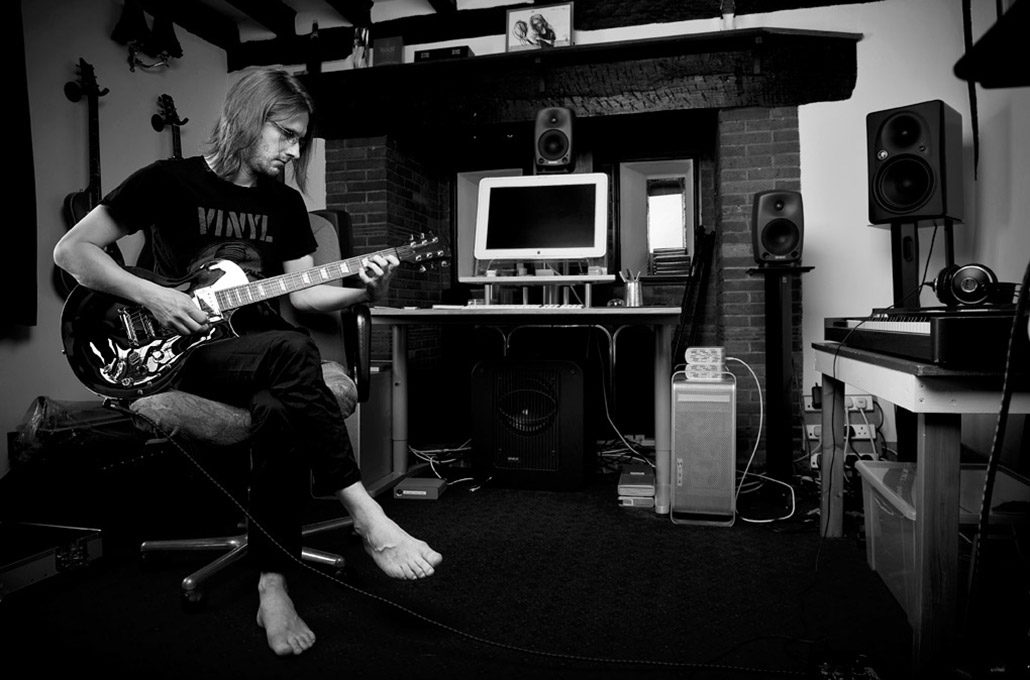 Steven Wilson of Porcupine tree playing guitar in his home studio photographed by Marcus Maschwitz