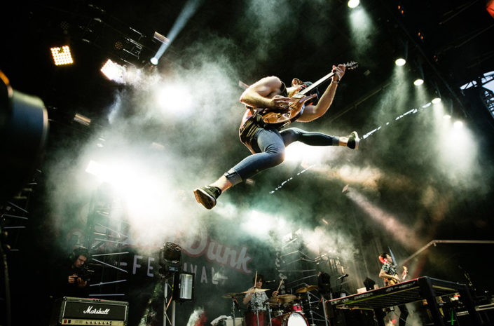 Simon De Laney of Don Broco jumping on stage photographed by Marcus Maschwitz